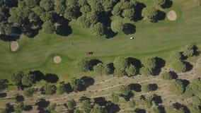 有运转在高尔夫球场的贷款刈草机的一台拖拉机 股票视频