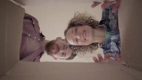 有胡子的人和微笑的妇女倾斜在箱子和神色里面,微笑 幸福家庭在移动以后打开事在新房里 股票视频