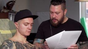 有胡子的纹身花刺艺术家谈论剪影与他的男性客户 影视素材