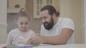 有胡子的爸爸和美丽的小的女儿油漆与flamasters在桌上坐一个休息日 消遣父亲和 股票录像
