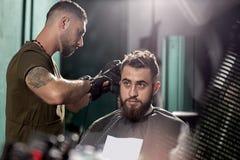 有胡子的英俊的年轻人坐在理发店 理发师刮头发在边 免版税库存图片