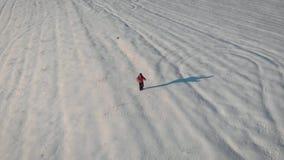 有背包和迁徙的棍子的一个人反对冬天山背景,美好的日落,在小山的雪 A 影视素材