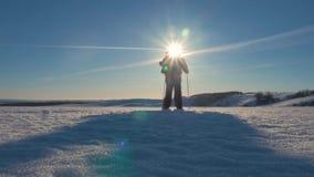 有背包和迁徙的棍子的一个人反对冬天山背景,美好的日落,在小山的雪 A 股票录像