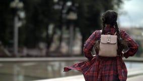 有背包的女孩跑,后面视图 免版税库存图片