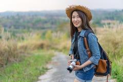 有背包的女性游人和照相机在乡下 库存图片