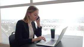 有膝上型计算机的女孩讲话在电话在咖啡馆桌上在冬天 股票录像