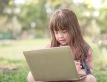 有膝上型计算机的小女孩 库存照片