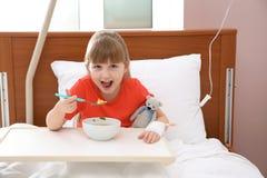 有静脉内滴水的小孩吃汤的 库存照片