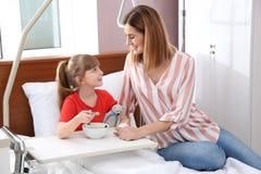 有静脉内滴水的小孩在医院病床上的吃汤 免版税库存图片