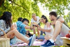 有饮料的在野餐的朋友和食物在公园 图库摄影