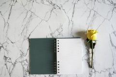 有黄色玫瑰色花的空白的螺纹笔记本在白色和灰色大理石背景 与拷贝空间的最小的设计 免版税图库摄影