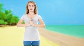 有闭合的眼睛的微笑妇女在热带海滩海洋海背景-夏天瑜伽概念,拷贝空间的Namaste姿势 库存照片