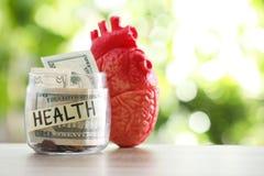 有金钱和心脏模型的玻璃瓶子在反对被弄脏的背景的桌上 免版税库存照片