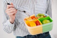 有长发的苗条深色的女孩在白色背景吃与从一个容器的一把叉子午餐的 颜色盒为 库存图片