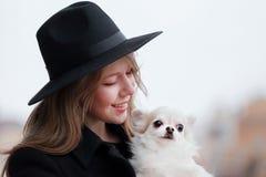 有长发的逗人喜爱的快乐的亭亭玉立的白种人女孩金发碧眼的女人在一黑色大衣和黑帽会议在秋天天有她白色小的 免版税库存图片