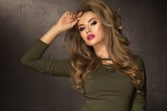 有长和发光的卷发的白肤金发的时尚女孩 图库摄影