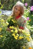 有长的头发嗅到的花的美丽的白肤金发的小女孩 库存图片