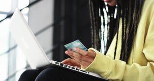 有dreadlocks的细节特写镜头非洲夫人使用信用卡做一种网上交易在她的笔记本她 影视素材