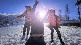 朋友公司获得乐趣在度假在冬天山 一个人和两个女孩享受冬天在滑雪 股票录像
