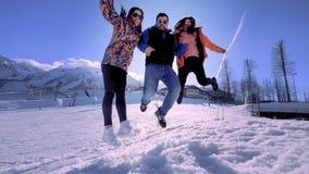 朋友公司获得乐趣在度假在冬天山 一个人和两个女孩享受冬天在滑雪 股票视频