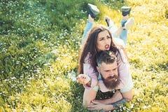 抽烟嗜好概念 在爱的夫妇花费时间户外和抽烟 放置在草春日的男人和妇女 夫妇 库存照片