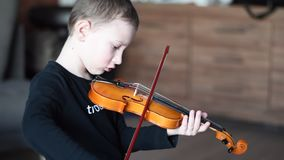 把柄举行小提琴 小男孩运载的小提琴 弹小提琴,有天才的小提琴球员的年轻男孩 股票视频