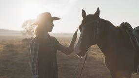 抚摸和拥抱马的牛仔帽的白肤金发的女孩 美丽的马妇女 股票视频