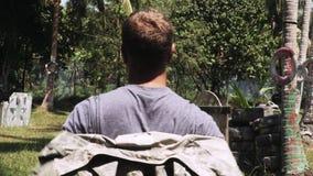 投入在迷彩漆弹运动比赛的伪装衣服的男性球员在与轮胎和木避难所的迷彩漆弹运动领域在森林 股票录像