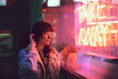 接触她的头发的年轻女人看通过玻璃在与一个窗口的一家俱乐部旁边与霓虹灯拿走 免版税库存照片