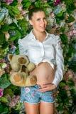 接触她的腹部的怀孕的愉快的妇女 怀孕的年轻母亲画象,爱抚她腹部和微笑 健康怀孕 库存图片