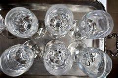 接近在一个银色盘子的一些空的玻璃酒杯子非常清洗准备好在餐馆使用在党 免版税库存图片