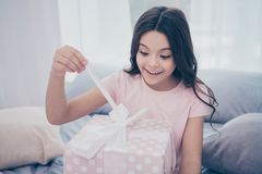 接近的照片甜情感地美丽她她的女孩坐的床举行打开的当前箱子最佳的天佩带 免版税库存照片