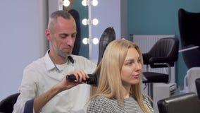成熟男性一个女性客户的美发师吹干的头发沙龙的 股票视频