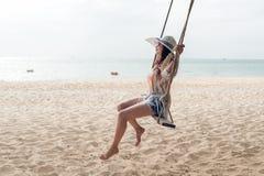 我其他看到暑假工作 放松和享受在沙子海滩的生活方式妇女摇摆,塑造有白色礼服的惊人的妇女在tr 图库摄影