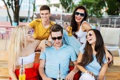 戴太阳镜笑和喝黄色鸡尾酒和交往在桌上的悦目朋友公司 免版税图库摄影