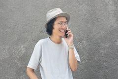 戴帽子和眼镜的一个可爱的年轻亚裔人使用smarphone 库存图片