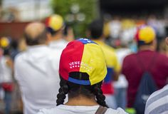 戴着委内瑞拉旗子帽子的妇女在抗议 免版税库存照片