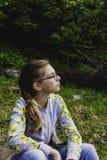 戴眼镜的哀伤的体贴的青少年的女孩在森林里坐单独自然 免版税图库摄影