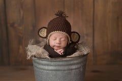 戴猴子帽子的新出生的男婴 免版税库存照片