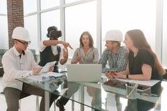 戴虚拟现实眼镜的设计师在与企业队的一次会议上 免版税库存图片