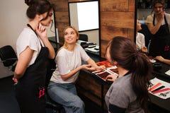 显示从调色板的微笑的白肤金发的年轻女人发色到她的美发师在上色前在发廊 beauvoir 库存图片