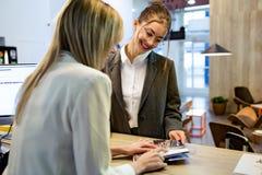 显示他们的服务的率确信的秀丽recepcionist对一个女性客户在旅馆的招待会 免版税库存图片