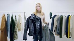 显示外套和皮夹克的年轻俏丽的女推销员在试衣间 影视素材