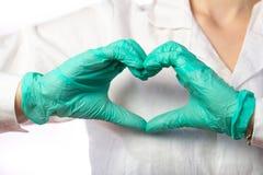 显示心脏姿态,关闭的手套的护士  免版税库存照片