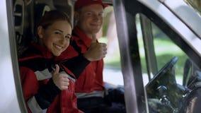 显示赞许,专家的救护车乘员组当班提供急救 免版税库存图片