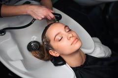 旁边vew有吸引力,有坐闭合的眼睛的美女,当在发廊时的美发师洗涤的头发 beauvoir 库存照片