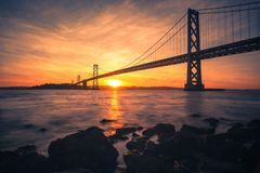 日出在SF奥克兰海湾桥梁下 免版税库存照片