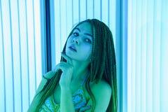 日光浴室 有非洲辫子的俏丽的女孩在东方舞蹈的一件礼服晒日光浴在垂直的sunbed 蓝色霓虹焕发 免版税库存照片