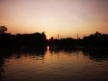 日落阴云密布天空反射在水中 库存图片