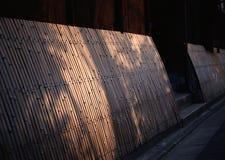 日语有太阳光芒的持续的竹墙壁 库存照片